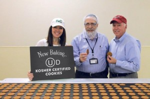 CEO, STEPHANIE LINDLEY, OU KOSHER FIELD REP, RABBI NORMAN SCHLOSS, CHAIRMAN EMERITUS BENNY CURL STAND WITH THE FIRST OU CERTIFIED COOKIES.
